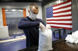 In this Thursday, March 26, 2020 photo, A.J. Davidson, who works in the business development department at Blue Delta Jeans, packages face guards made at the jeans manufacturing site in Shannon, Miss.