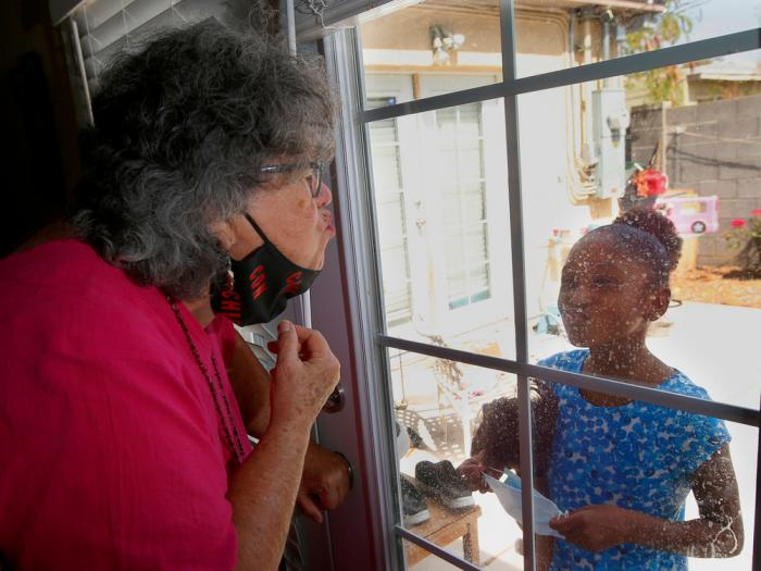 """Zita Robinson, left, who's 77 and diabetic, blows a kiss to her granddaughter Traris """"Trary"""" Robinson-Newman, 8, who blows a kiss back to her, Tuesday, Aug. 4, 2020, in Phoenix"""