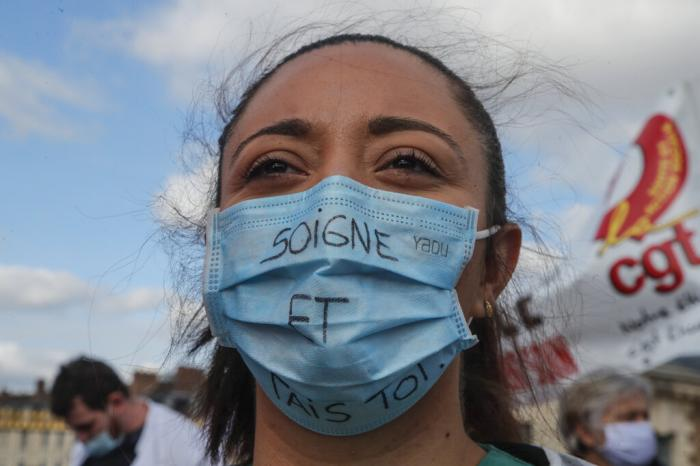 "A medical worker wears as mask that reads ""heal and shut up,"" as she demonstrates to demand better salaries and working conditions in Paris, Thursday, Oct. 15, 2020."
