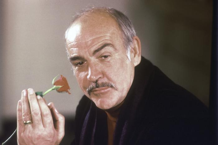 """Sean Connery holds a rose in his hand as he talks about his new movie """"The Name of the Rose"""" in 1987."""
