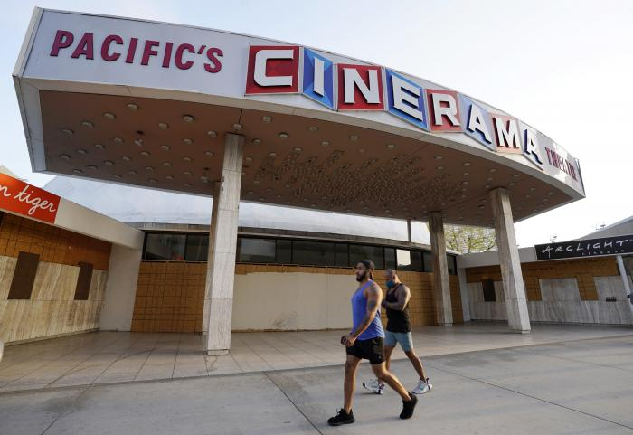 Pedestrians walk past the boarded up and closed Cinerama Dome movie theater.