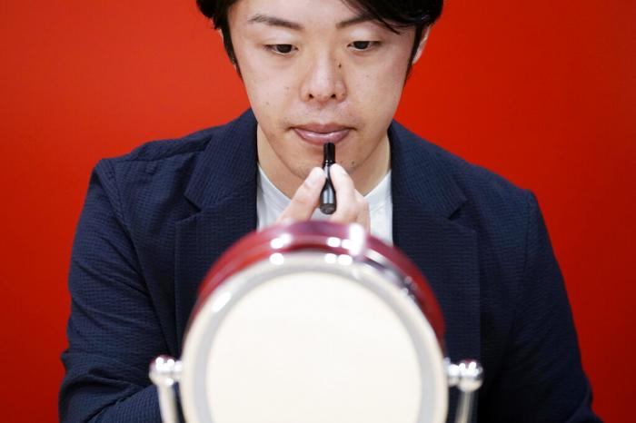 Naruhiko Ito, assistant brand manager of Brand Shiseido Group, demonstrates the brand's latest lip balm for men.