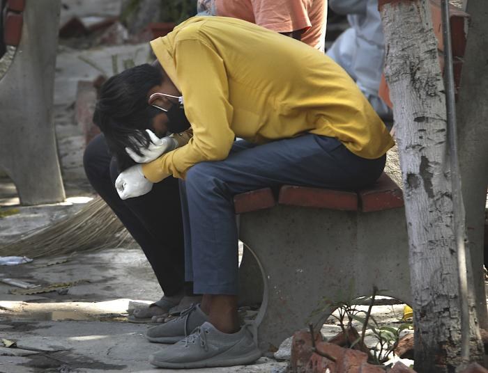 A relative of a person who died of COVID-19 reacts during cremation, in New Delhi, India.