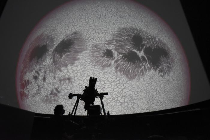 Researcher Ivannia Calvo, silhouetted against a solar satellite image, works inside the Solar Astronomical Observatory in San Jose, Costa Rica, Friday, April 30, 2021