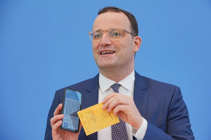 Jens Spahn (CDU), Federal Minister of Health, shows the Corona Warn app with a sample digital vaccination certificate.